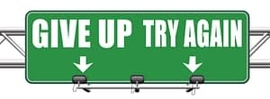 """Road sign which points in different directions, """"give up"""" and """"try again"""""""