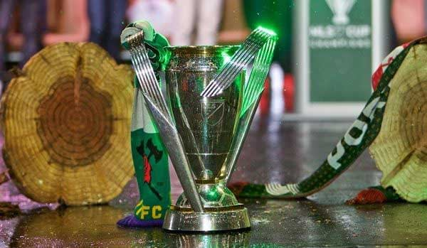 The MLS Cup trophy stands next to two logs, signifying Portland Timbers' 2015 victory.