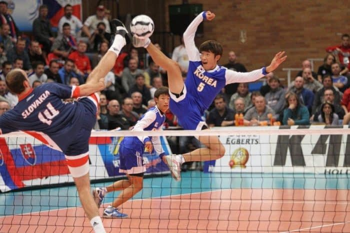 Two players stretch to win the ball at the Futnet World Championship.