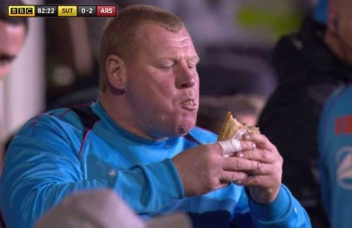 Wayne Shaw eats a pie during Sutton United's clash with Arsenal.