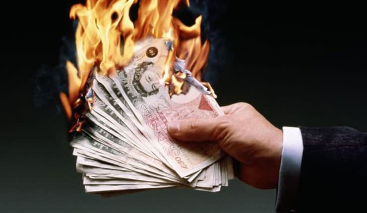 Man burning £50 notes.