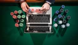 A hand places poker chips on a laptop.