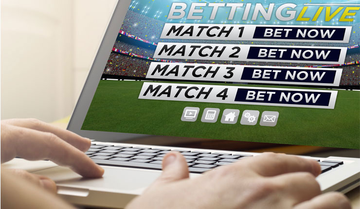 Man using a laptop to place football bets.