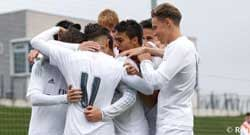 Real Madrid Castilla players huddle together after scoring a goal.