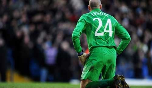 Brad Friedel, goalkeeper for Tottenham Hotspur, kneeling on a football pitch.