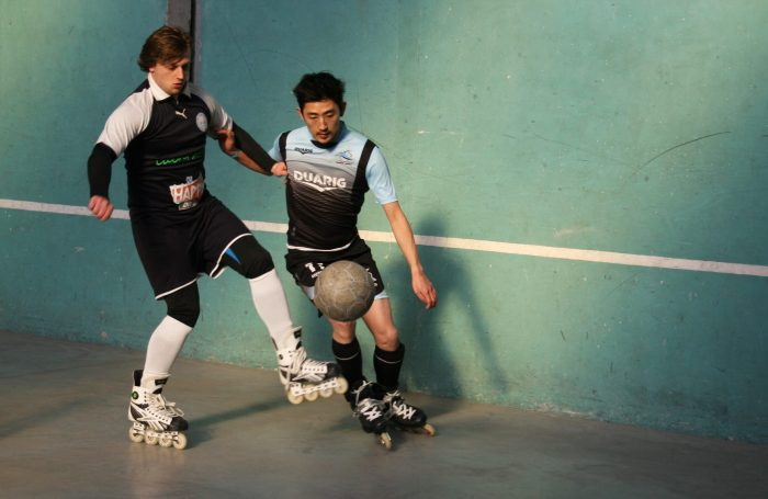 Two roller soccer players compete to win possession of the ball.