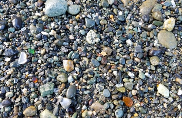 Image of clear, brown and green sea glass laying on Glass Beach, Port Townsend.