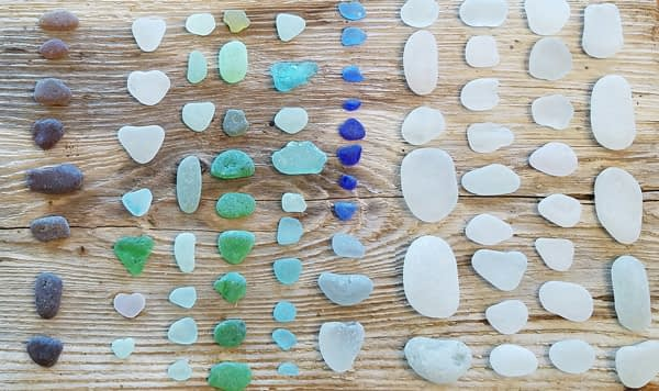Brown, green, aqua, blue and white sea glass from Glass Beach, Port Townsend on a wood table background.
