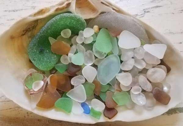 Clam shell full of green sea glass, aqua sea glass, brown sea glass and clear or white sea glass.