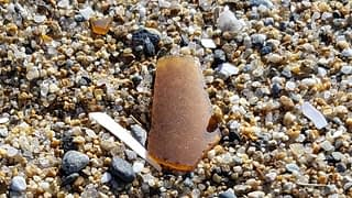 Borwn sea glass in the sand at Old Orchard Beach, Maine.