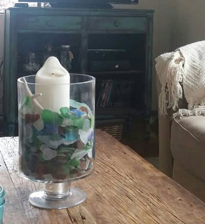 Large vase filled with sea glass sitting on table