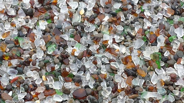 Smooth pieces of white, green and brown sea glass on the beach at Fort Bragg, California.