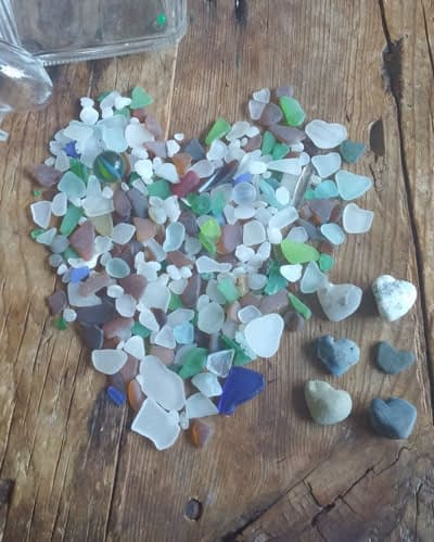 Large pile of Capo Beach sea glass shaped into a heart on a table
