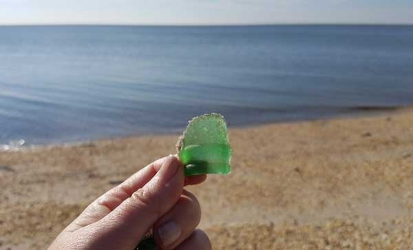 Hand holding a piece of smooth wave tumbled green sea glass on the beach in New Jersey.