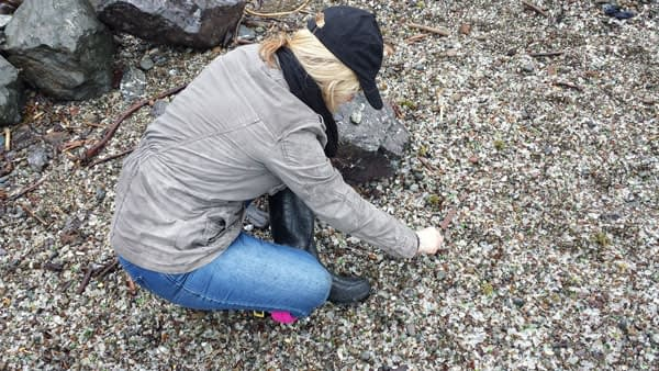 Woman hunting for rare colors of sea glass at Glass Beach, Fort Bragg.
