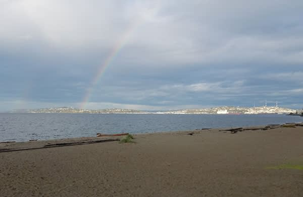 Image of a rainbow over Puget Sound while sea glass hunting at Alki Beach, Washington.