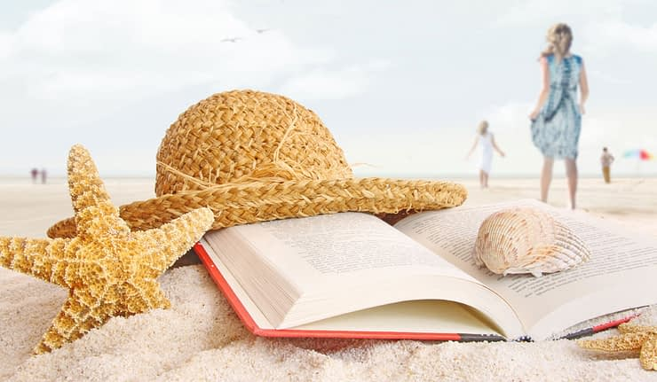 Book, starfish, shell and hat on the beach