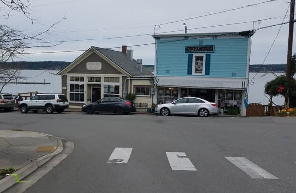 View of Aqua Gifts and Kneed & Feed at Main street and Front street in Historic waterfront Coupeville, Washington.