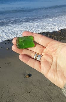 Piece of green sea glass in hand on the beach with sand and waves behind