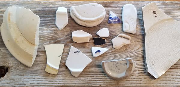 Old sea pottery found on the beach near the Historic Coupeville Wharf on Whidbey Island, Washington placed on a piece of old barn wood.