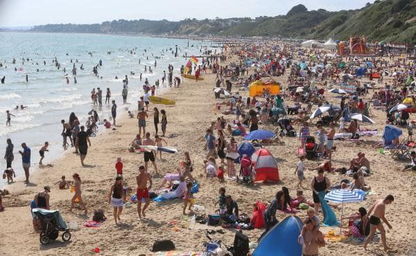 Crowds flock to Southbourne Beach, Bournemouth, Dorset at the first sign of sunshine.