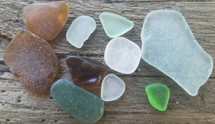 Green sea glass, brown sea glass, clear sea glass on driftwood background.from Long Beach Island, New Jersey.
