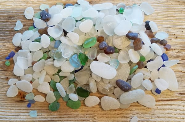 Blue, aqua, green, brown and white sea glass from Glass Beach, Port Townsend laying on a wood table.