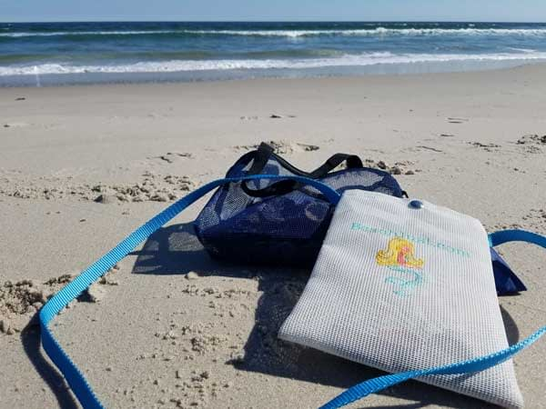 Sea glass hunting bags in the sand with ocean waves in back ground.