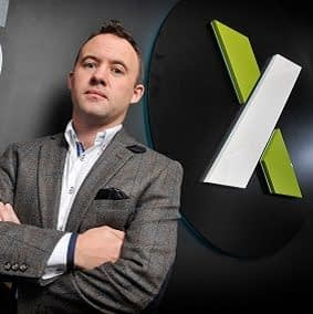 CEO Mark Brosnan stands infront of the Xanadu Consultancy logo.