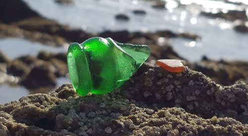 Sea glass bottle neck on rocks in Laguna Beach, California