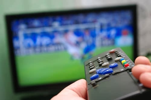 a TV remote being pointed at a television while a football match is being played.