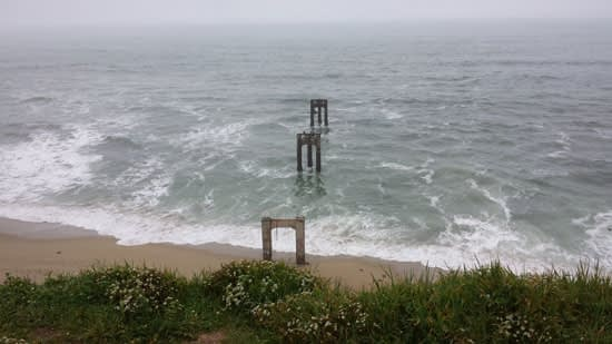 View from above the old Santa Cruz Portland Cement Company pier ruins with strong waves crashing on the shore.