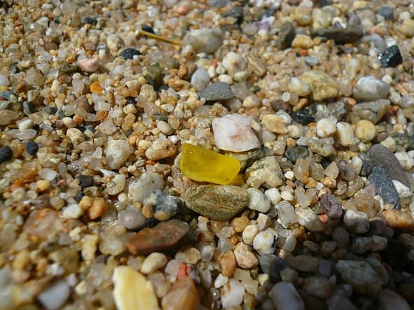 A piece of yellow sea glass laying on top of sea shells.