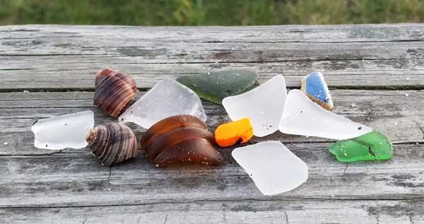 Smooth sea glass and sea pottery on a wood background.