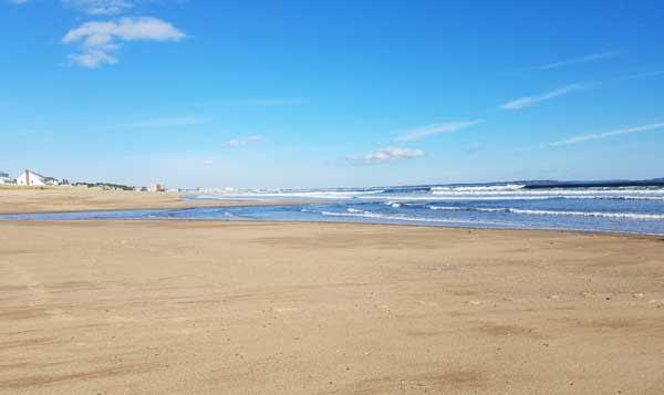 Sandy beach and blue ocean at Kinney Shores Beach, Maine.