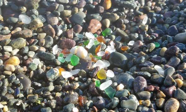 Sea glass in several colors such as green, brown, aqua sea glass, teal sea glass and clear sea glass on a pebbly beach at 40 Steps Beach in Nahant, Massachusetts.