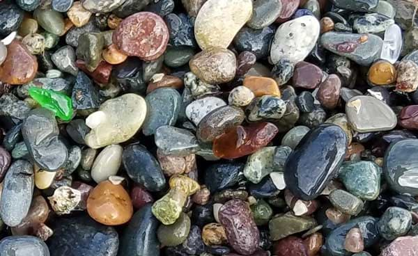 Image of brown sea glass laying on colorful pebbles on 40 Steps Beach, Nahant, Massachusetts.