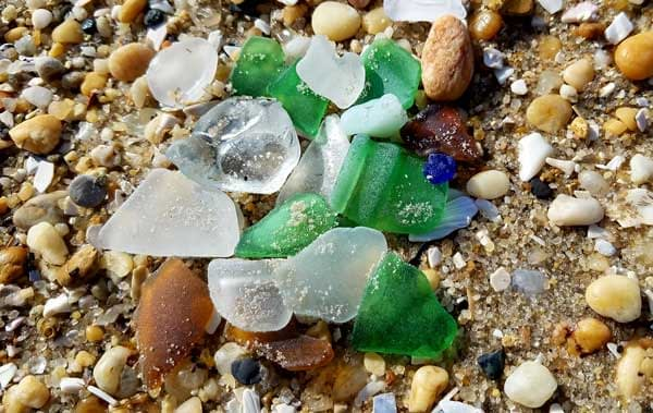 Many pieces of green, blue, brown and white sea glass laying on the sand at the beach.