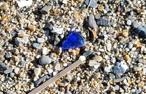 Blue sea glass in the sand at Kinney Shores Beach, Maine.