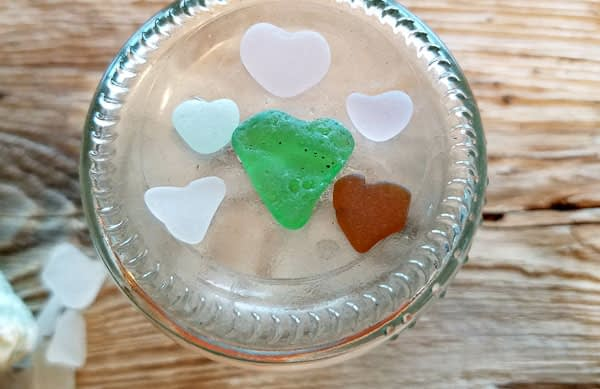 Sea glass hearts in green, brown, clear, aqua and lavender Manganese glass or sun glass collected from the beaches in Washington State on an upsidedown jar placed on a wood table.
