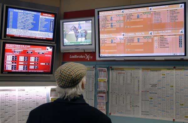 A man checks the results of an event at a betting shop.