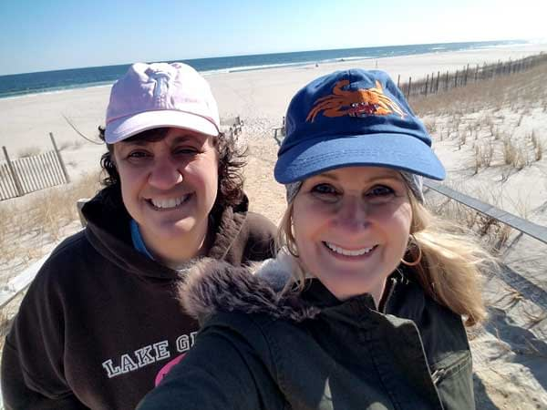 Two ladies on Long Beach Island looking for sea glass on the beach with sand and ocean in the back ground.