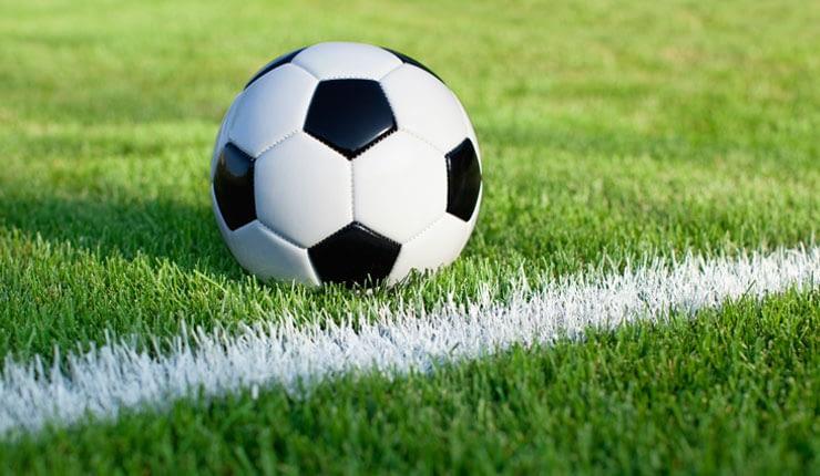 Football on grass next to white chalk line.