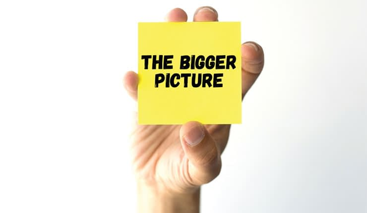 "A man holding up a yellow sticky note with ""THE BIGGER PICTURE"" written in black text."