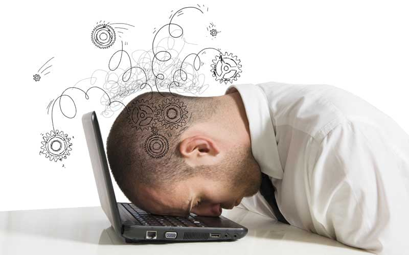 A frustrated man banging his head against his laptop computer.